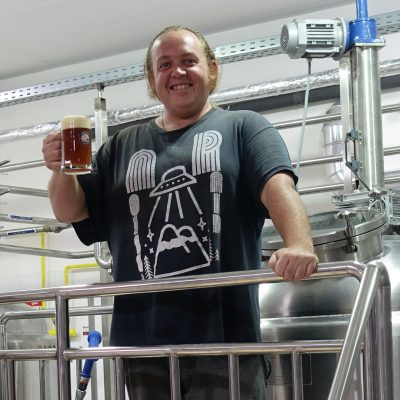 Head Brewer smiling with a glass of beer
